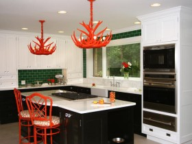 Black and white kitchen with red stools and chandeliers