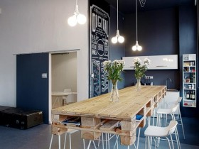 Blue and white kitchen with wooden table made of pallets