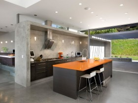 Black kitchen island with orange countertops in the cottage style of constructivism