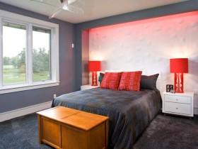 Яркая спальня ў шэрых танах з чырвонымі свяцільнямі і драўляным куфрам