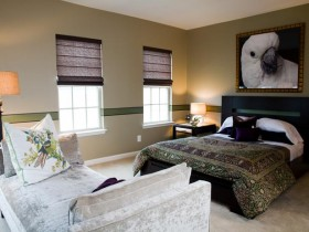 Bedroom interior in contrasting shades with a picture of a parrot on the bed