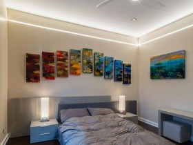 Modern and bright bedroom with colourful paintings