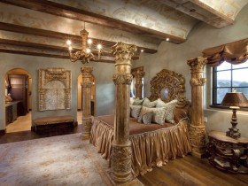 Luxurious bedroom in a medieval style with columns and rich wooden furniture