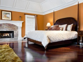 Bedroom orange color with a white ceiling and a fireplace