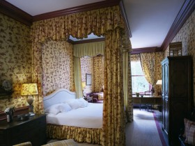 Bedroom with a private office and a four-poster bed