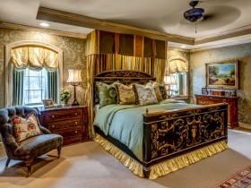 Раскошная спальня з класічнай драўлянай мэбляй і залацістым тэкстылем