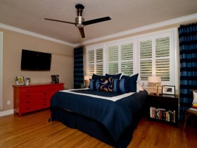 Bright bedroom with dark blue bed and red drawers