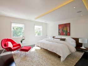 Contemporary bedroom with hidden ceiling light and a red chair
