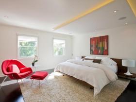 Сучасная спальня са схаванай потолочной падсветкай і чырвоным стульчиком