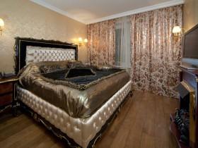 Спальня з вялікай драўлянай ложкам, аздобленай пазалотай