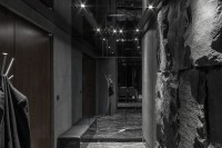 Black entrance hall with stone wall and glass Cabinet